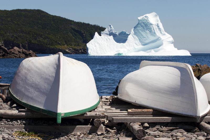 An iceberg passing a fishing village