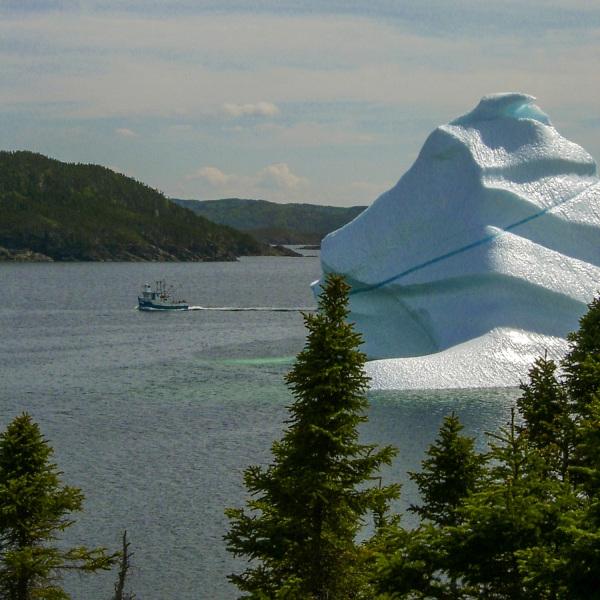 An iceberg dwarfs a fishing boat