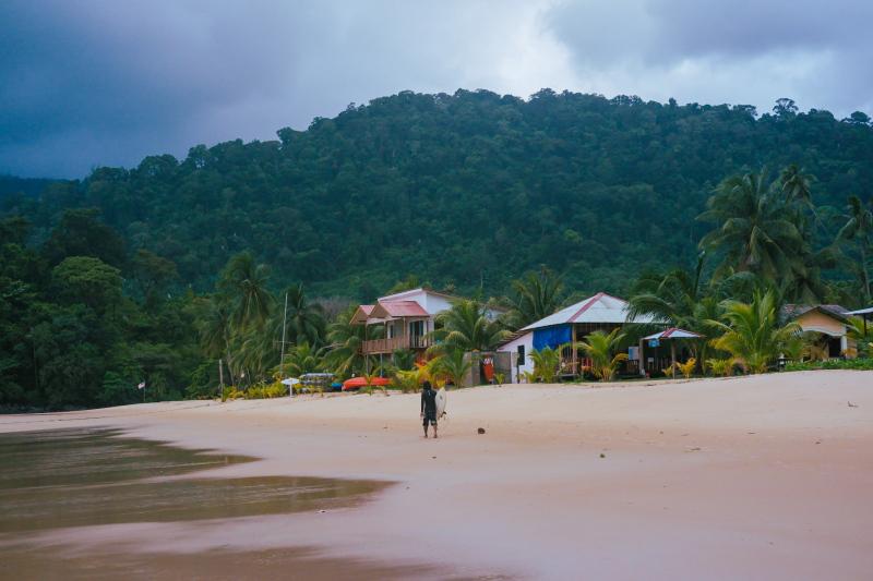 A lone surfer on a beach on Tioman Island